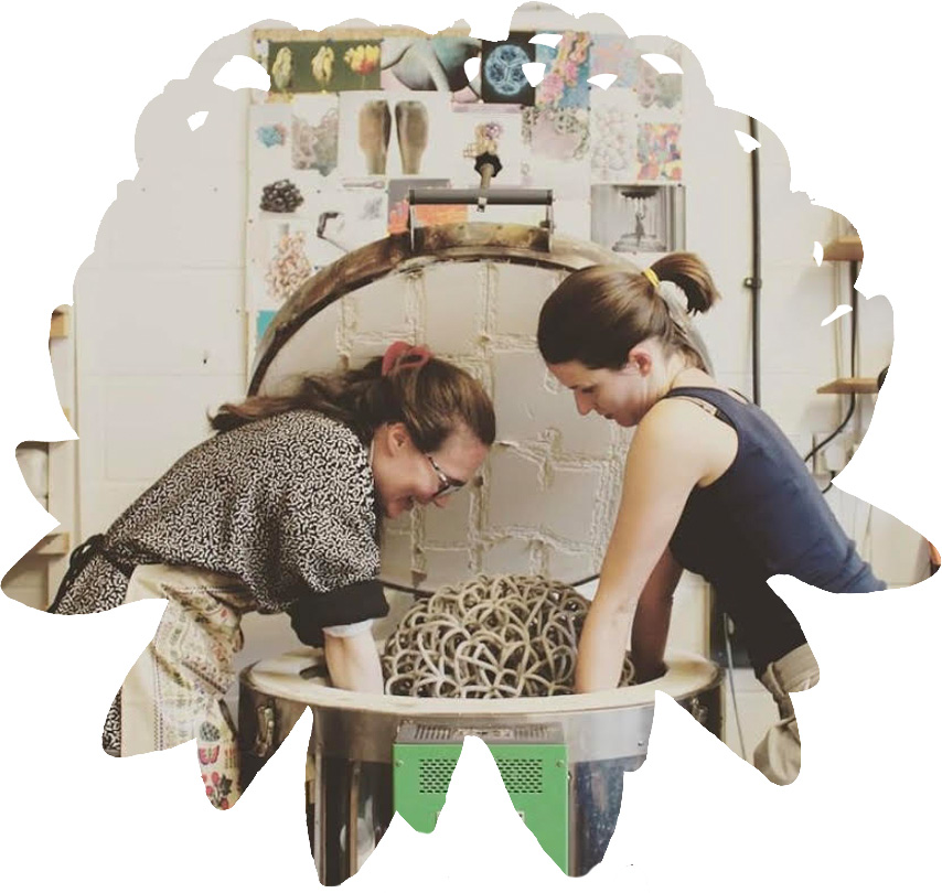 Tessa Eastman and ceramicist lifting a ceramic sculpture out of a kiln